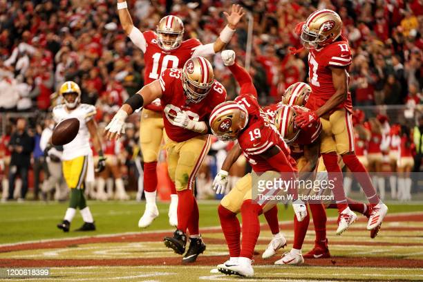 Jimmy Garoppolo and Ben Garland of the San Francisco 49ers celebrate a touchdown in the second quarter against the Green Bay Packers during the NFC...
