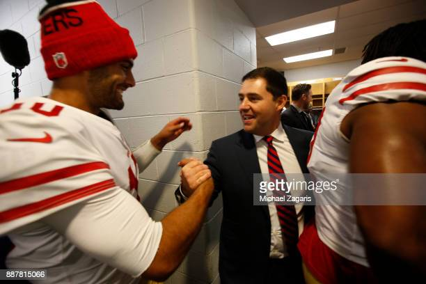 Jimmy Garoppolo and CEO Jed York of the San Francisco 49ers celebrate in the locker room follwoing the game against the Chicago Bears at Soldier...