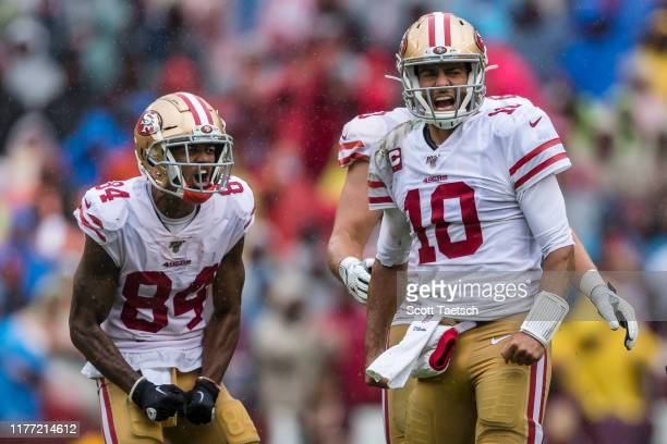 Jimmy Garoppolo and Kendrick Bourne of the San Francisco 49ers reacts after gaining a first down \W| during the first half at FedExField on October...