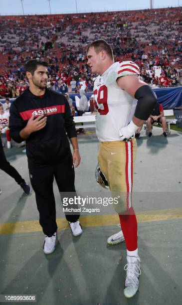 Jimmy Garoppolo and Mike McGlinchey of the San Francisco 49ers talk on the sideline during the game against the Los Angeles Rams at the LA Memorial...