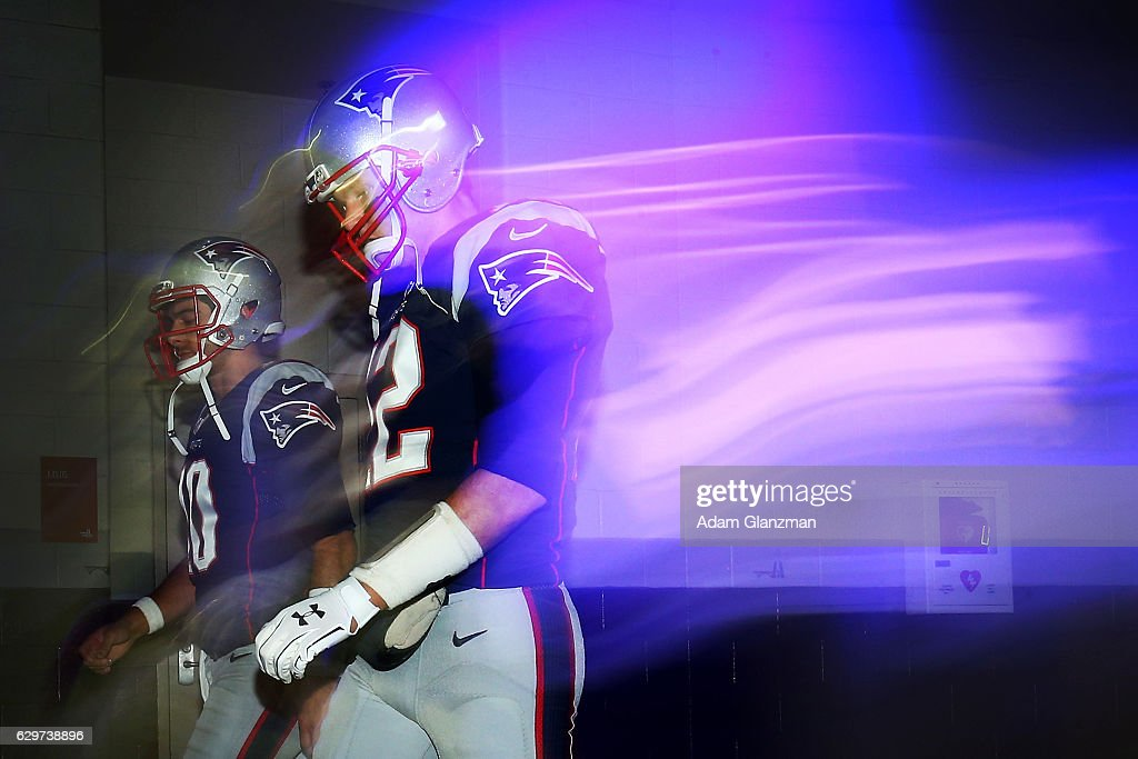 Jimmy Garoppolo #10 (L) and Tom Brady #12 of the New England Patriots walk through the tunnel prior to the game against the Baltimore Ravens at Gillette Stadium on December 12, 2016 in Foxboro, Massachusetts.