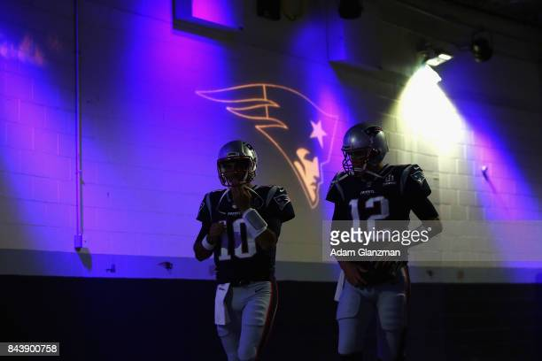 Jimmy Garoppolo and Tom Brady of the New England Patriots walk to the field before the game against the Kansas City Chiefs at Gillette Stadium on...