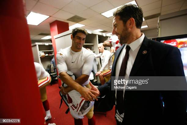 Jimmy Garoppolo and Vice President of Player Personnel Adam Peters of the San Francisco 49ers celebrate in the locker room following the game against...