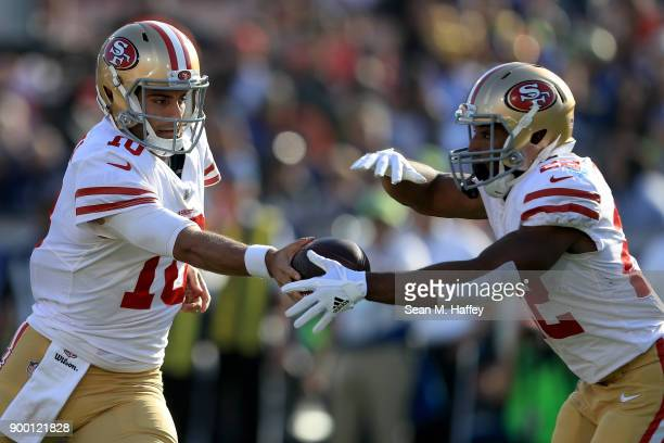 Jimmy Garoppolo hands off to Matt Breida of the San Francisco 49ers during the first half of a game against the Los Angeles Rams at Los Angeles...