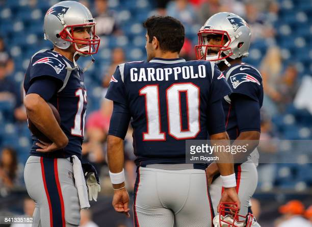 Jimmy Garoppolo Jacoby Brissett and Tom Brady of the New England Patriots chat before a preseason game with the New York Giants at Gillette Stadium...