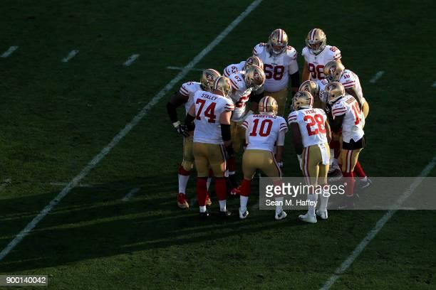 Jimmy Garoppolo leads a huddle with Joe Staley Carlos Hyde Elvis Dumervil Aldrick Robinson and Garrett Celek of the San Francisco 49ers during the...
