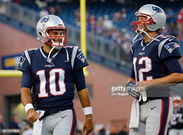 Jimmy Garoppolo of the New England Patriots and Tom Brady react before a preseason game with the New York Giants at Gillette Stadium on August 31...