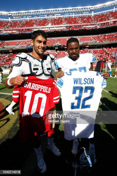 Jimmy Garoppolo of the San Francisco 49ers and Tavon Wilson of the Detroit Lions trade jerseys on the field following the game at Levi Stadium on...