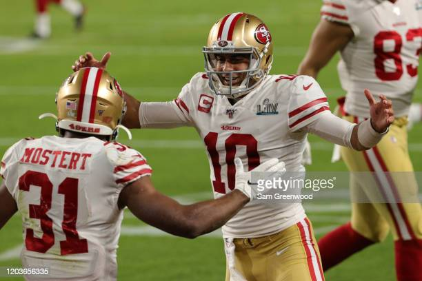 Jimmy Garoppolo of the San Francisco 49ers celebrates with Raheem Mostert after a touchdown against the Kansas City Chiefs during the third quarter...