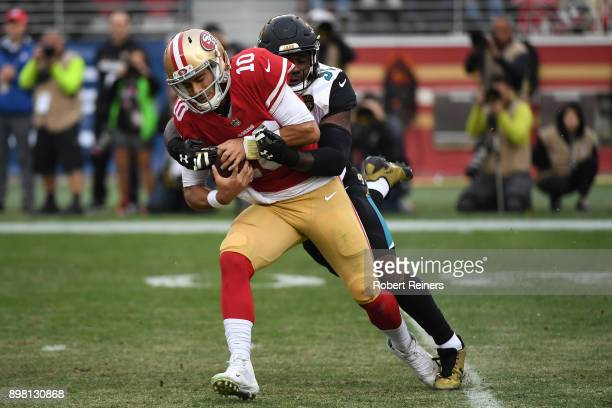 Jimmy Garoppolo of the San Francisco 49ers is sacked by Yannick Ngakoue of the Jacksonville Jaguars during their NFL game at Levi's Stadium on...