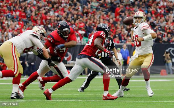 Jimmy Garoppolo of the San Francisco 49ers looks to pass under pressure by Andre Hal of the Houston Texans and Angelo Blackson in the second half at...