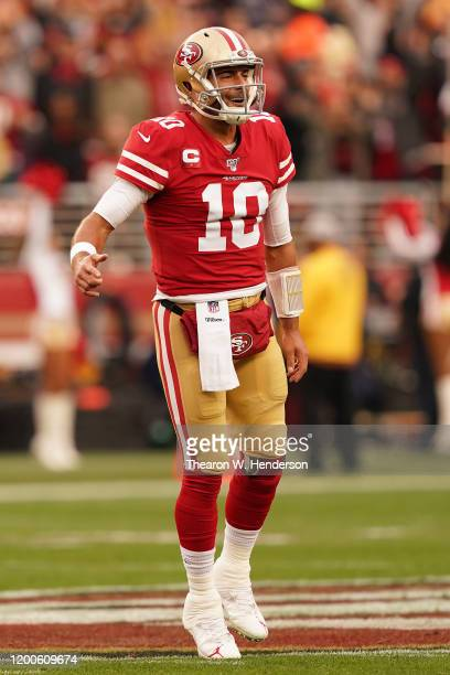 Jimmy Garoppolo of the San Francisco 49ers reacts to a touchdown run by Raheem Mostert in the first quarter against the Green Bay Packers during the...