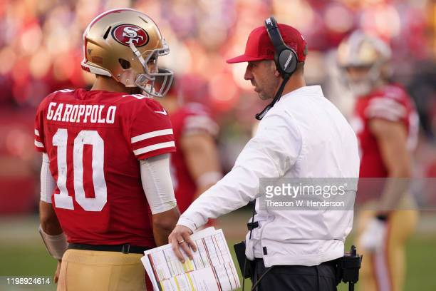 Jimmy Garoppolo speaks with head coach Kyle Shanahan of the San Francisco 49ers during the NFC Divisional Round Playoff game against the Minnesota...