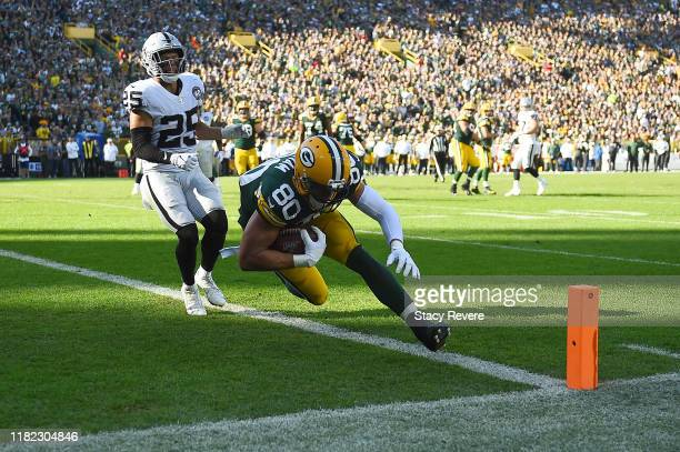 Jimmy Graham of the Green Bay Packers catches a pass for a touchdown in front of Erik Harris of the Oakland Raiders during the third quarter of a...