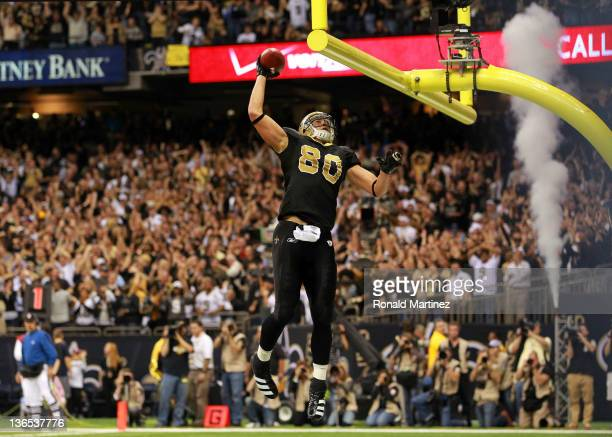 Jimmy Graham of the New Orleans Saints celebrates by dunking the football over the crossbar after scoring a touchdown in the third quarter against...
