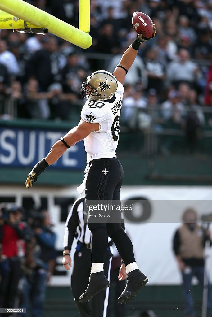 Jimmy Graham #80 of the New Orleans Saints dunks the ball over the goal posts after he scored a touchdown against the Oakland Raiders at O.co Coliseum on November 18, 2012 in Oakland, California.