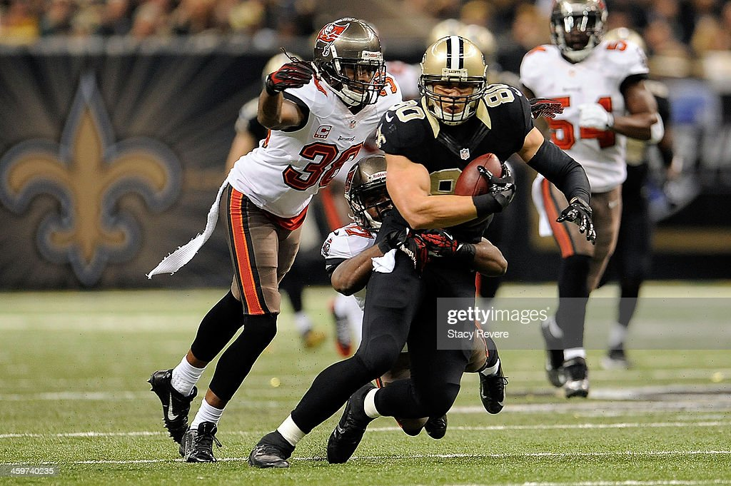 Jimmy Graham #80 of the New Orleans Saints is brought down by Johnthan Banks #27 and Dashon Goldson #38 of the Tampa Bay Buccaneers during a game at the Mercedes-Benz Superdome on December 29, 2013 in New Orleans, Louisiana. New Orleans won the game 42-17.