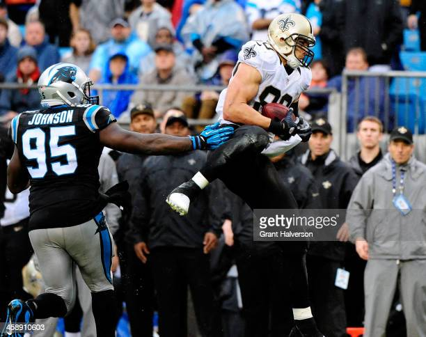 Jimmy Graham of the New Orleans Saints makes a catch as Charles Johnson of the Carolina Panthers looks on during their game at Bank of America...