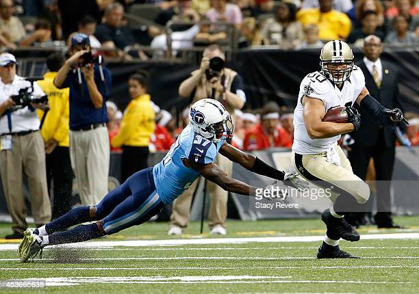 Jimmy Graham of the New Orleans Saints runs the ball as Tommie Campbell of the Tennessee Titans tries to tackle him during a preseason game at the...