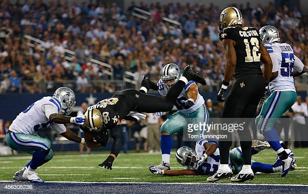 Jimmy Graham of the New Orleans Saints scores a touchdown as Rolando McClain of the Dallas Cowboys tries to make the stop in the second half at ATT...