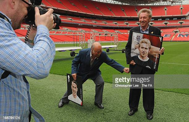 Jimmy Greaves jokes around by pretending to pull Denis Law's trousers down as he has his photograph taken with his stamp during the Royal Mail Stamp...