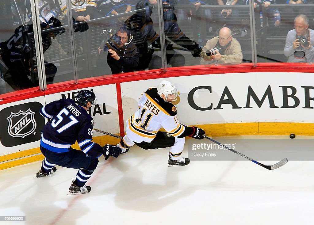 Jimmy Hayes #11 of the Boston Bruins and Tyler Myers #57 of the Winnipeg Jets chase the puck along the boards during third period action at the MTS Centre on February 11, 2016 in Winnipeg, Manitoba, Canada.