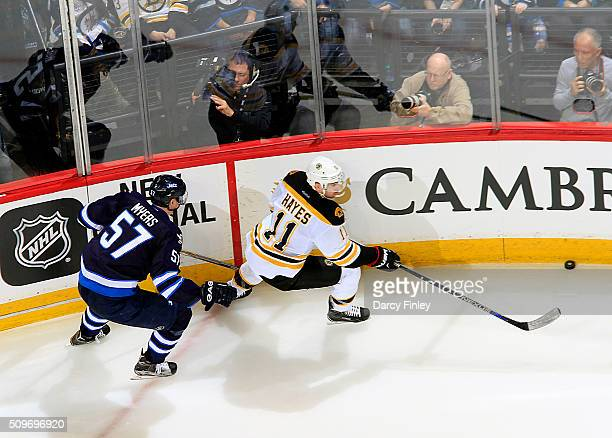 Jimmy Hayes of the Boston Bruins and Tyler Myers of the Winnipeg Jets chase the puck along the boards during third period action at the MTS Centre on...