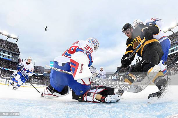 Jimmy Hayes of the Boston Bruins crashes the net as goaltender Mike Condon of the Montreal Canadiens makes a save in the second period during the...