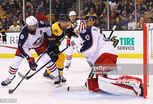 Jimmy Hayes of the Boston Bruins looks for a shot against Curtis McElhinney of the Columbus Blue Jackets while being defended by Seth Jones during...