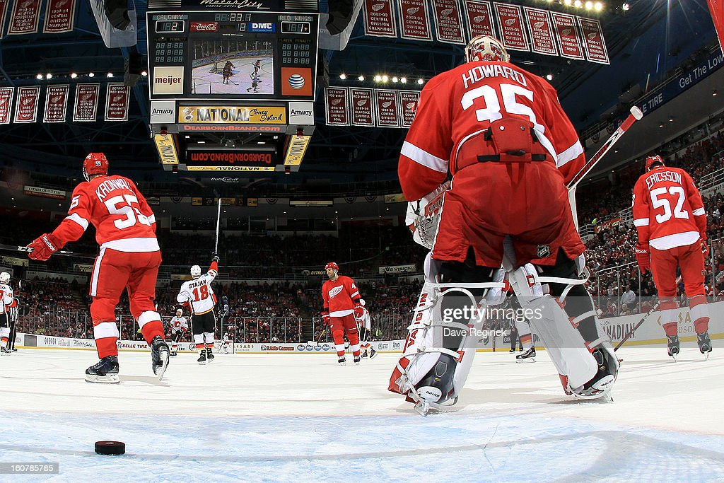 Jimmy Howard #35, Niklas Kronwall #55 and Jonathan Ericsson #52 of the Detroit Red Wings watch the Calgary Flames celebrate after scoring a goal during a NHL game at Joe Louis Arena on February 5, 2013 in Detroit, Michigan. Calgary defeated Detroit 4-1