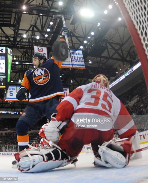 Jimmy Howard of the Detroit Red Wings can't stop a first period shot by Rob Schremp of the New York Islanders as Jon Sim celebrates in front at the...