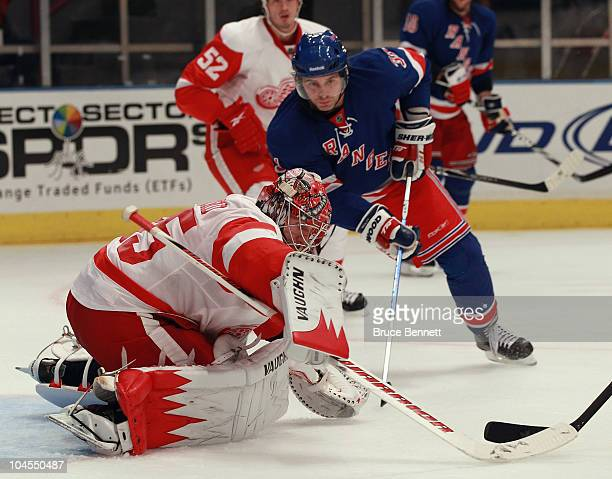 Jimmy Howard of the Detroit Red Wings covers the puck as Alex Frolov of the New York Rangers looks for a rebound at Madison Square Garden on...