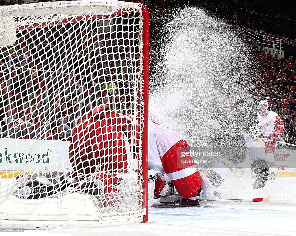 Jimmy Howard #35 of the Detroit Red Wings covers the puck as Sidney Crosby #87 of the Pittsburgh Penguins sprays him with ice during an NHL game on March 20, 2014 at Joe Louis Arena in Detroit, Michigan.