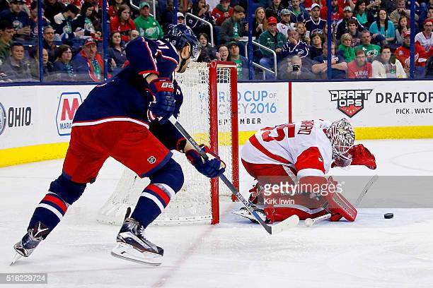 Jimmy Howard of the Detroit Red Wings covers up the puck before Nick Foligno of the Columbus Blue Jackets can get to the rebound during the second...