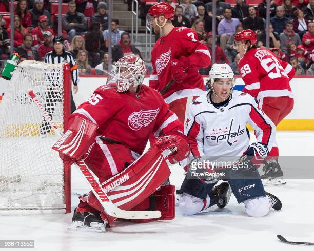 Jimmy Howard of the Detroit Red Wings follows the play with teammate Nick Jensen as TJ Oshie of the Washington Capitals reaches for his stick during...
