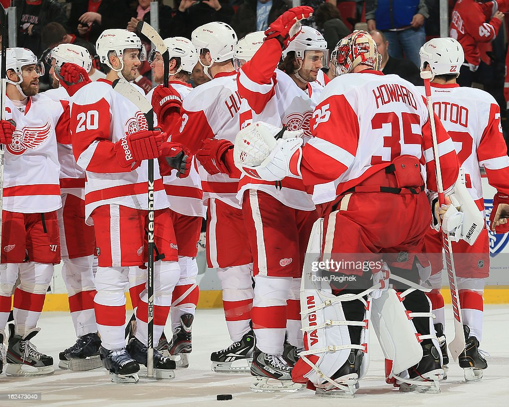 Jimmy Howard #35 of the Detroit Red Wings is congratulated by his teammates after earning a 4-0 shut out against the Nashville Predators at Joe Louis Arena on February 23, 2013 in Detroit, Michigan.