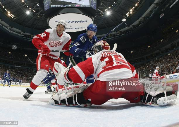 Jimmy Howard of the Detroit Red Wings looks on as teammate Jonathan Ericsson and Henrik Sedin of the Vancouver Canucks look for a rebound during...