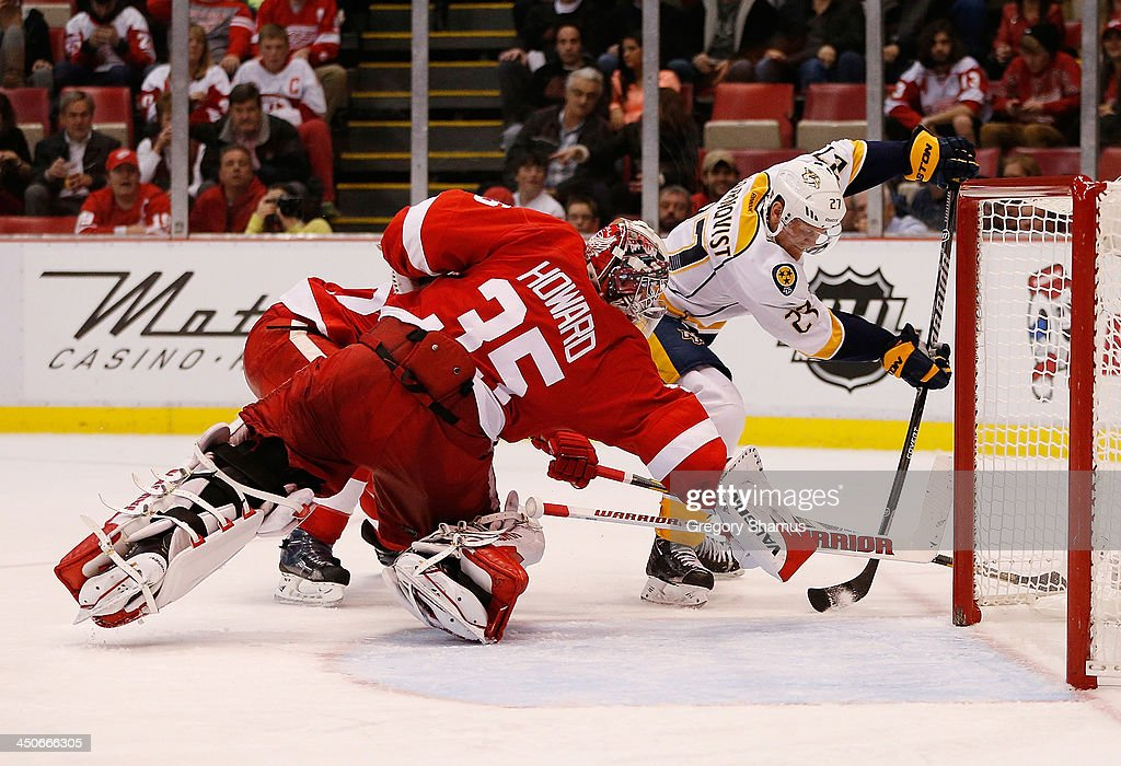 Jimmy Howard #35 of the Detroit Red Wings makes a diving save against Eric Nystrom #24 of the Nashville Predators in the third period at Joe Louis Arena on November 19, 2013 in Detroit, Michigan. Nashville won the game 2-0.