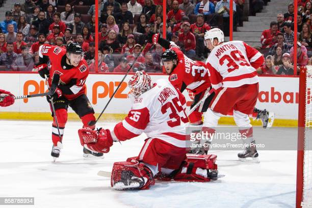 Jimmy Howard of the Detroit Red Wings makes a glove save against Ryan Dzingel of the Ottawa Senators as Fredrik Claesson of the Ottawa Senators and...