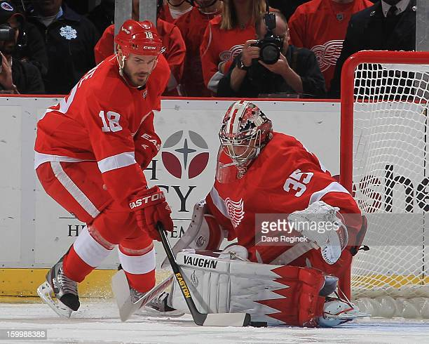 Jimmy Howard of the Detroit Red Wings makes a leg pad save as teammate Ian White helps to cover the puck during an NHL game against the Dallas Stars...
