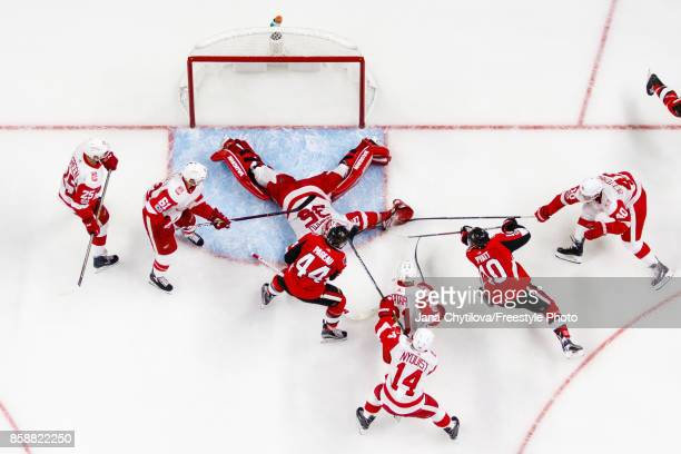 Jimmy Howard of the Detroit Red Wings makes a save against JeanGabriel Pageau of the Ottawa Senators as a scramble ensues in the crease in the third...