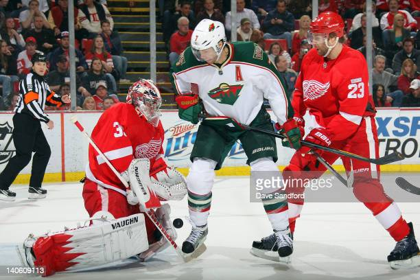 Jimmy Howard of the Detroit Red Wings makes a save as teammate Brad Stuart battles for the rebound with Matt Cullen of the Minnesota Wild during a...