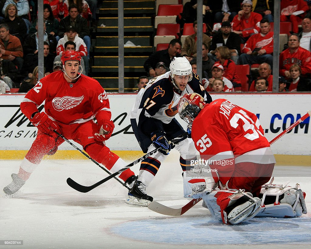 Jimmy Howard #35 of the Detroit Red Wings makes a save as teammate Jonathan Ericsson #52 keeps his eye on the puck along with Rich Peverley #47 of the Atlanta Thrashers during a NHL game at Joe Louis Arena on November 25, 2009 in Detroit, Michigan.
