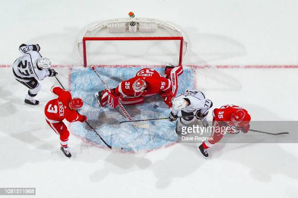Jimmy Howard of the Detroit Red Wings makes a save as teammates Nick Jensen and Niklas Kronwall battle in front with Dustin Brown and Jeff Carter of...