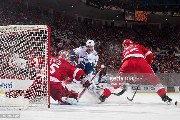 Jimmy Howard of the Detroit Red Wings makes a save on Matt Bartkowski of the Vancouver Canucks as teammate Niklas Kronwall defends during an NHL game...