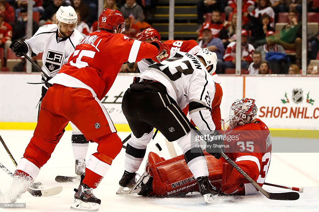 Jimmy Howard #35 of the Detroit Red Wings makes a third period save next to Dustin Brown #23 of the Los Angeles Kings at Joe Louis Arena on December 15, 2016 in Detroit, Michigan. Los Angeles won the game 4-1.