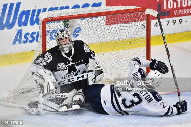 Jimmy Huntington of the Rimouski Oceanic crashes into goaltender Emile Samson of the BlainvilleBoisbriand Armada during the QMJHL game at Centre...