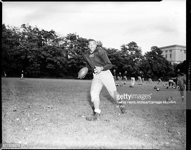 Jimmy Joe Robinson wearing University of Pittsburgh football uniform, holding football, on field with practice equipment in background, Pittsburgh,...