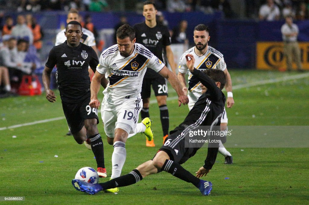 Jimmy Medranda #94 and Illie Sanchez #6 of Sporting Kansas City defend against Chris Pontius #19 of the Los Angeles Galaxy at StubHub Center on April 8, 2018 in Carson, California.