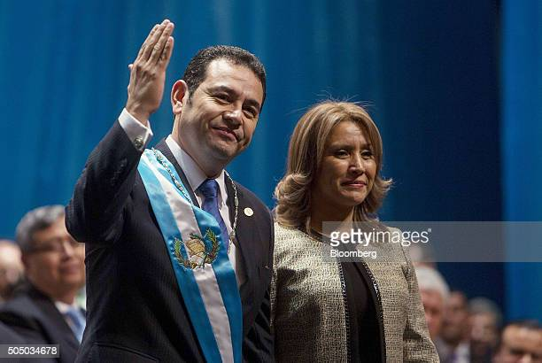Jimmy Morales, Guatemala's new president, left, waves while standing with his wife Hilda Patricia Morales during his inauguration in Guatemala City,...
